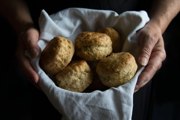 Two hands either side of a basket of scones
