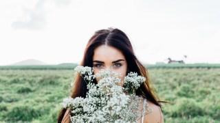 草原の中で花を持つ女の人