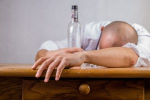 Bald man slumped over a table with an empty bottle of alcohol