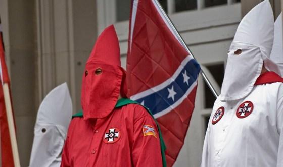 Ku Kux Klan con sus vestimentas típicas delante de una bandera de la Confederación de Estados Unidos. Autor: Martin, 21/11/2009. Fuente: Flickr. (CC BY-ND 2.0.).