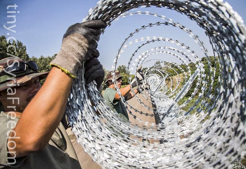 Los soldados húngaros levantando alambre de púas tras la crisis de refugiados. Autor: Freedom House, 09/09/2015. Fuente: Flickr