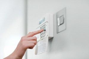 Woman setting burglar alarm --- Image by © Image Source/Corbis
