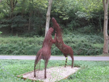 A metal sculpture of two horses rearing with their front hooves touching in the air