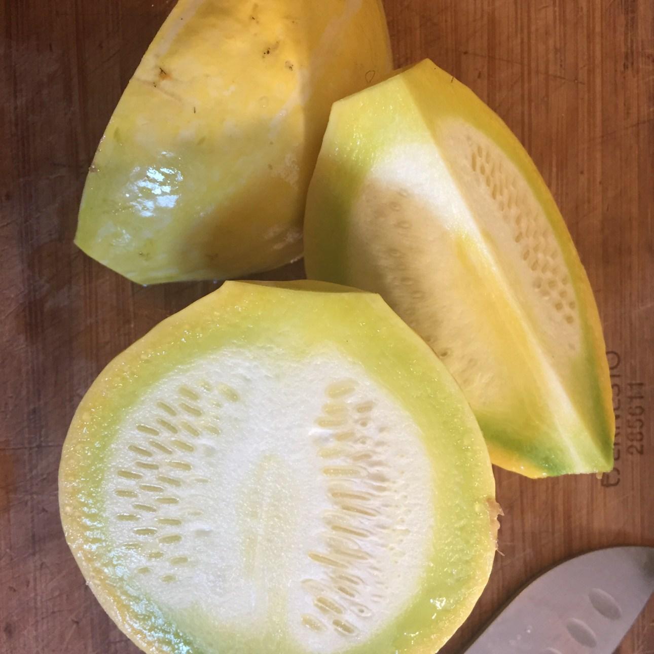 A yellow globe zucchini cut into three pieces