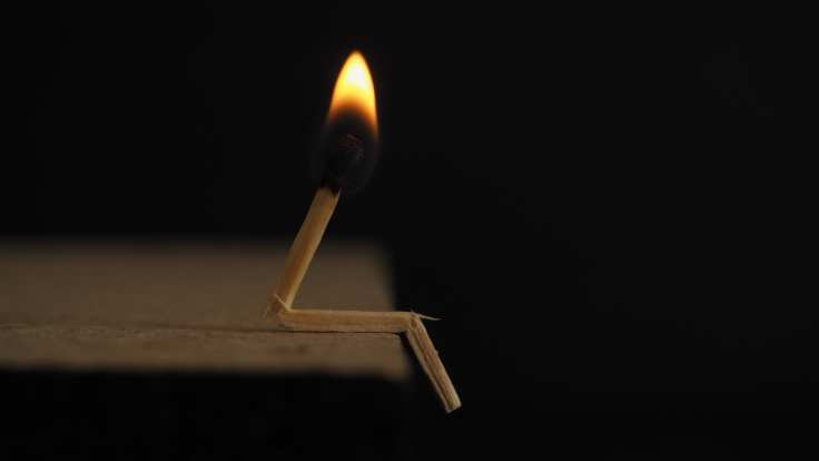 lighted matchstick on brown wooden surface