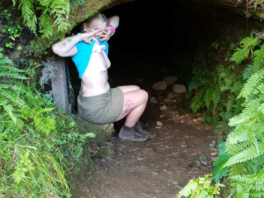 The barefoot sub with her tee shirt lifted, sitting at the mouth of the cave. for the scavenger hunt.
