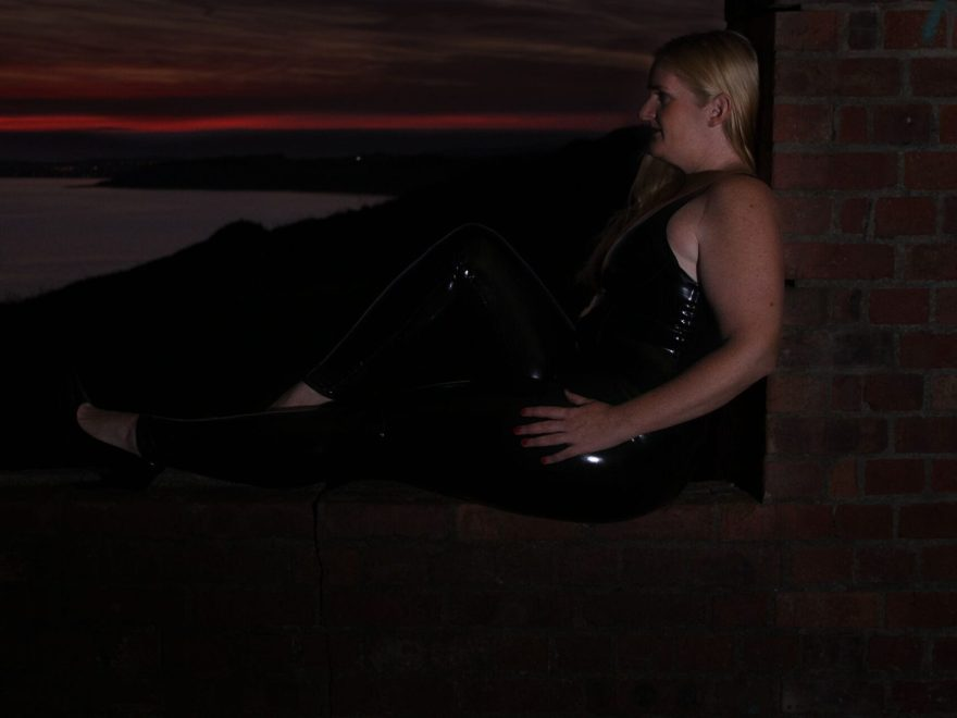 the barefoot sub on a brick wall, dressed in latex at sun down