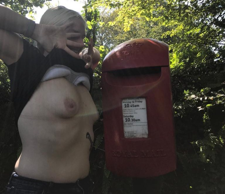 letter box adventure header image, the barefoot sub exposing her breasts at a post box