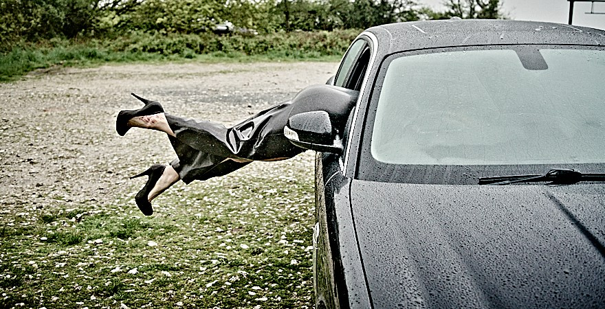 Kicking out in heels header, latex clad lady diving through a drivers side Jaguar window.
