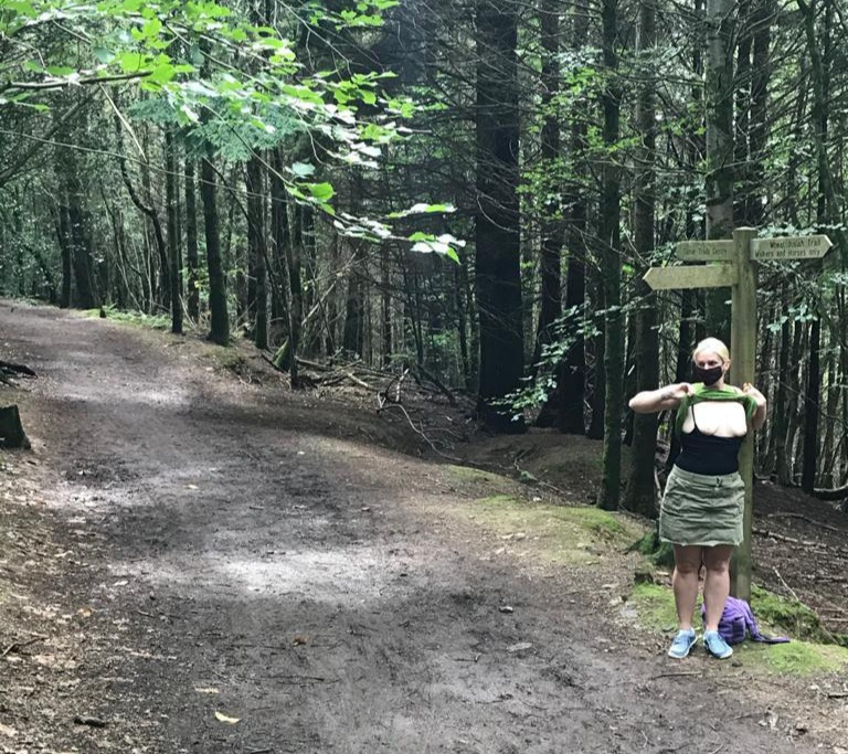 Sharing the footpath header, Barefoot is exposing her breasts on a muddy path through the woods, while standing under a signpost.