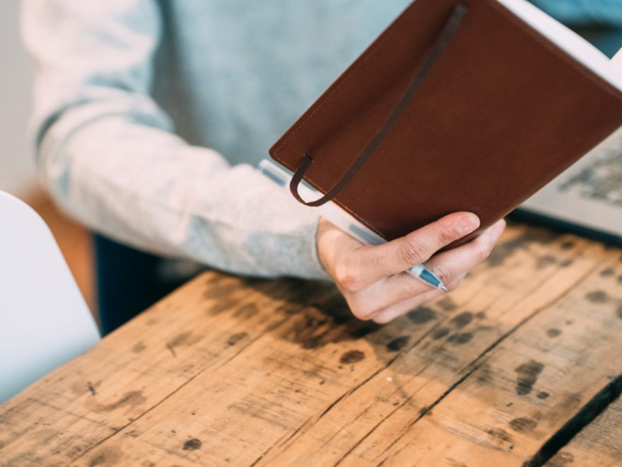 Blogable fiction marathon : My first DNF header image shows a hand holding a notebook and pen with the person sat at a wooden table with a laptop.