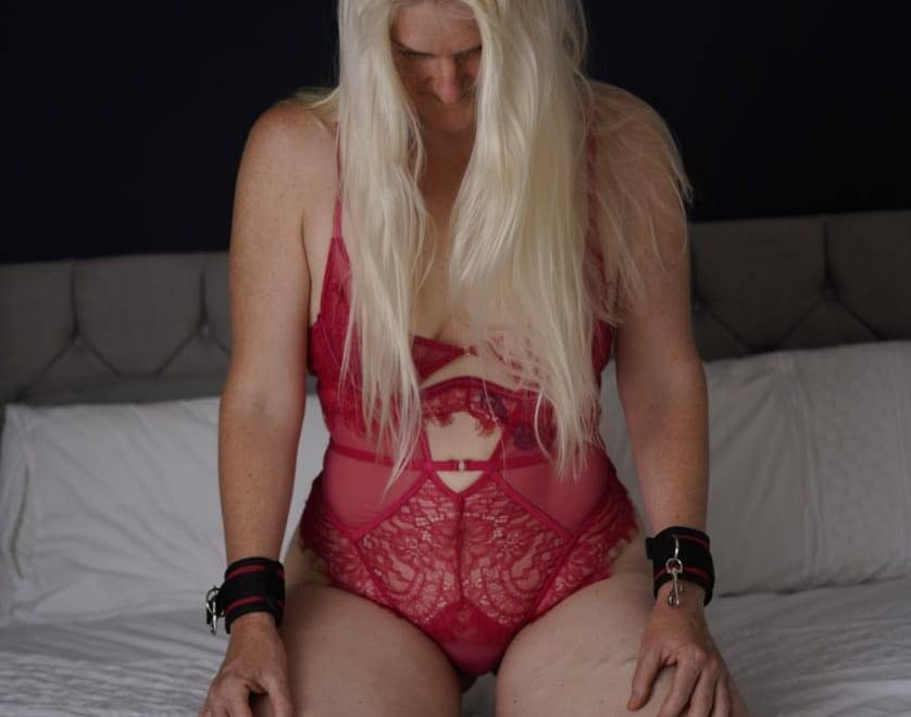 Kneeling in wait header image of the barefoot sub kneeling on a freshly made bed, wearing a scarlet lace body and wrist cuffs, with her long blonde hair flowing