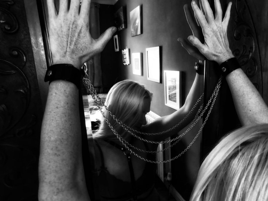 Down a dark alley? Not Today! Header image shows blonde woman leaning in towards a mirror, hands raised and pressed to the glass, wrists cuffed and joined with chains