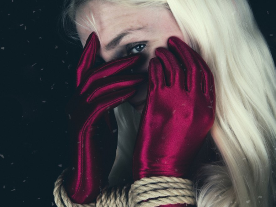 Creating the best day header image shows a woman with long blonde hair peeking through hands which are wearing long, red satin gloves and are bound at the wrist.