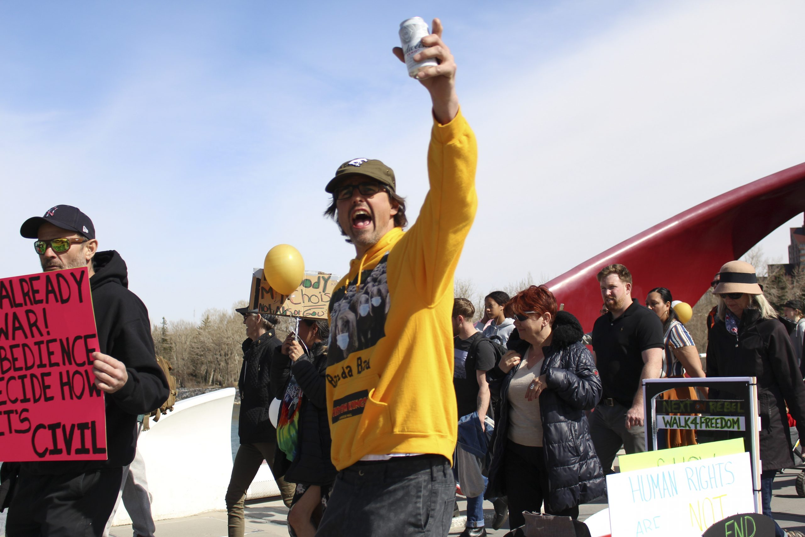 A man shouts and holds his can of beer to the sky while he marches with Walk for Freedom across the Peace Bridge toward the Sunnyside community in Calgary on April 3, 2021. Walk for Freedom is one of two organizations that protest against the COVID-19 restrictions, business closures, and the mask mandate. The Walk for Freedom group started rallying from the Princes Island Park stage before marching toward the bridge. (Photo by Alejandro Melgar/SAIT)