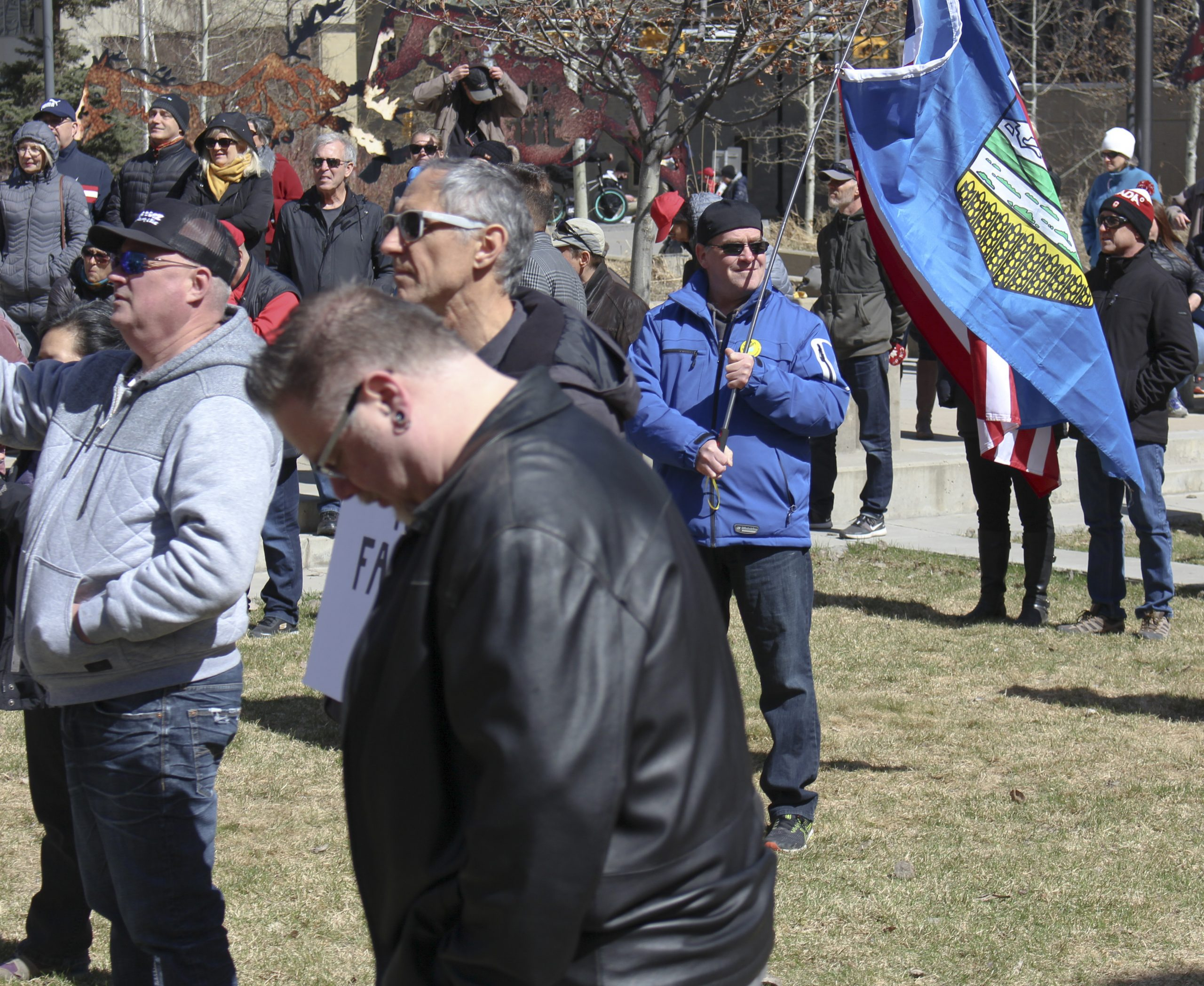 A man, amid a crowd, waves an Alberta and U.S. flag joined together while in attendance of the ÒSave Small BusinessÓ rally at Courthouse Park in downtown Calgary on April 11, 2021. A couple hundred people attended the event, hosted by Calgary Freedom Central, as a sign of support for the businesses that are facing hardships as a result of COVID-19 and the provincial lockdown, but also to express disdain for mask usage, vaccines, the COVID-19 testing method, and compliance with the government and the enforcement of said closures.(Photo by Alejandro Melgar/SAIT)