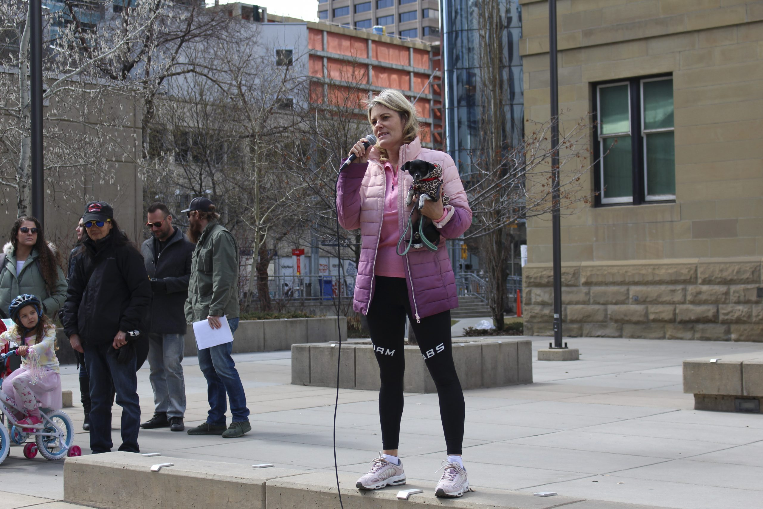 Belinda Morrison, founder of the CB Rescue Foundation, speaks to a crowd with her dog in hand at a rally that wants to save small businesses at Courthouse Park in downtown Calgary on April 11, 2021. Morrison is a self-proclaimed Master Trainer with 22 years of experience in the field. Her training business closed as a result of COVID-19, and she spoke to a crowd of a couple hundred about that struggle while citing the inhumane actions of the Alberta Government toward small businesses. Many speakers were also expressing disdain for mask usage, vaccines, the COVID-19 testing method, and compliance with the government and the enforcement of said closures. (Photo by Alejandro Melgar/SAIT)