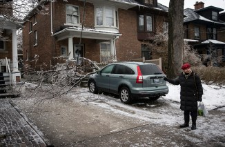 Julie Rozmanc reacts to a tree limb breaking from a tree and pulling down a power line on top of her car following an ice storm in Toronto