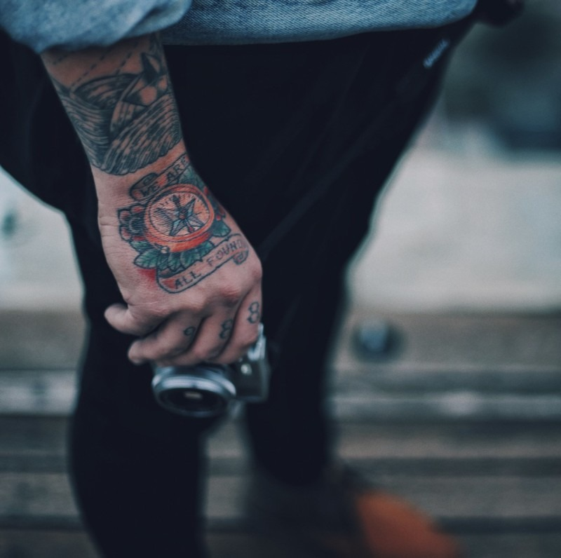 Tattooed hand holding a camera