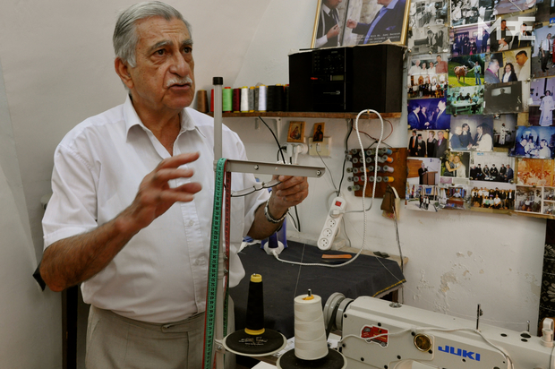 Photographs of politicians and celebrities adorn the wall of Sammy Barsoum's shop in what was once the Syriac Quarter of Jerusalem's Old City (MEE/Emily Mulder)