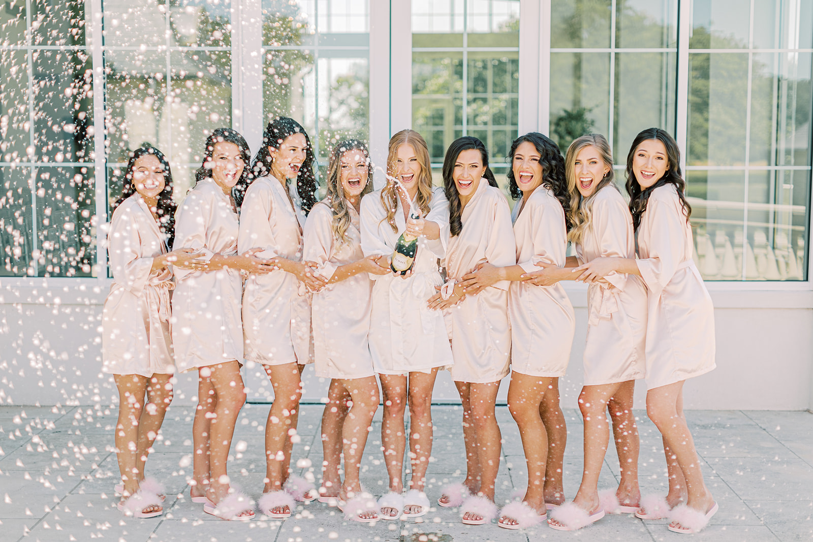 Bridal party in pink robes popping champagne
