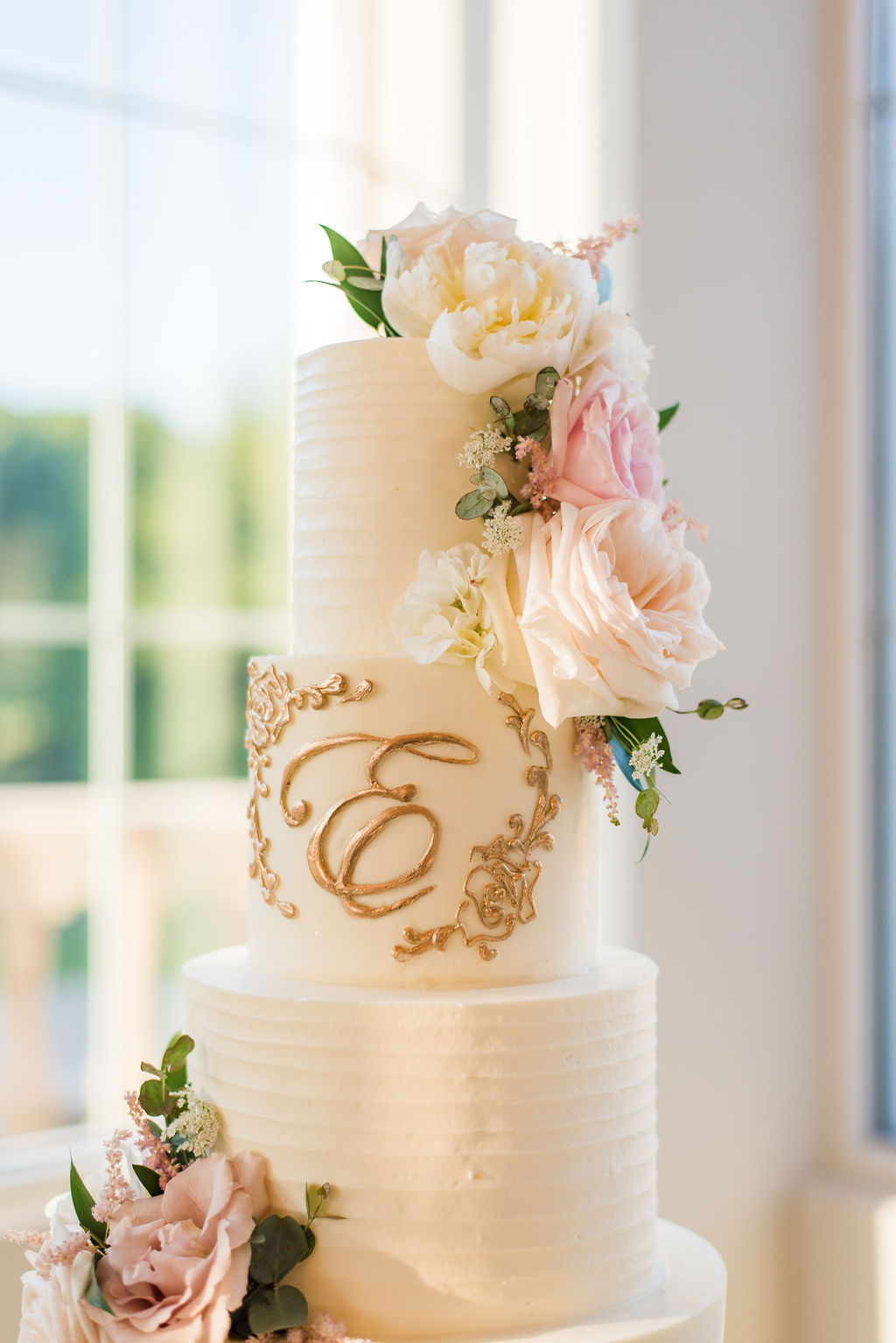 Monogrammed pink and white floral wedding cake