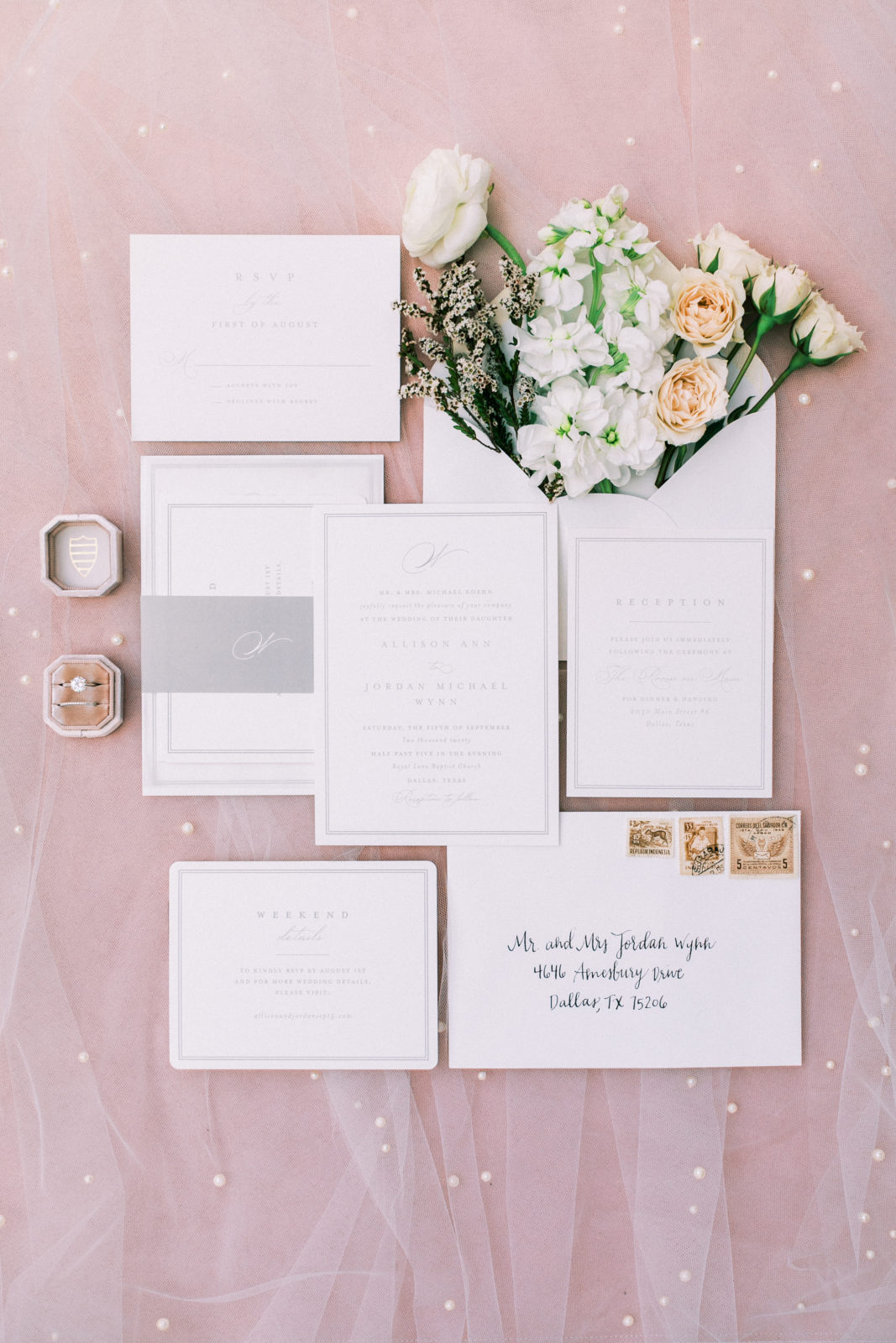 Classic white and black wedding invitation flatlay on pink backdrop