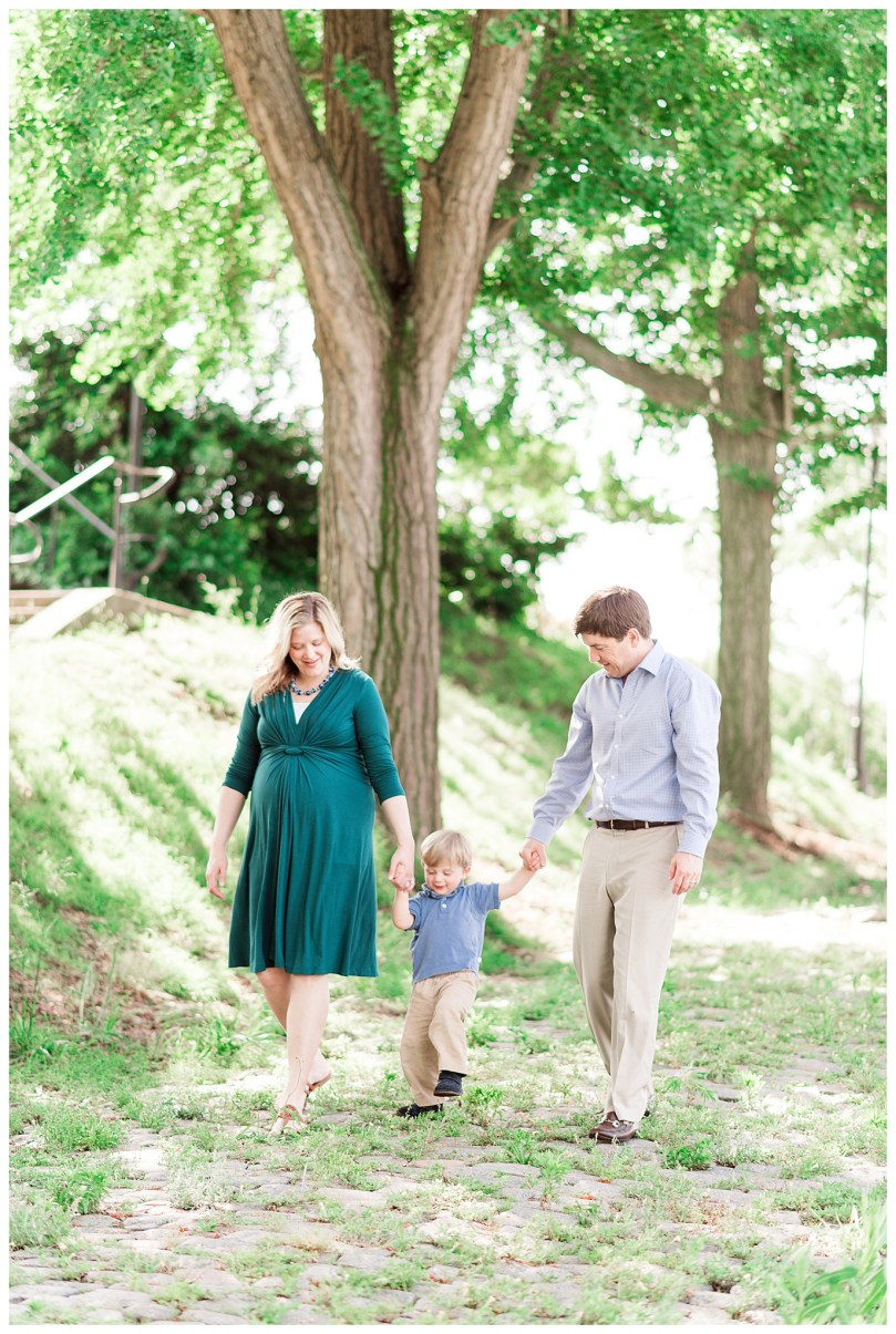 Emerald green maternity session at Libby Hill Park in Richmond Virginia. This family of three is welcoming a new baby in August. A two year old who loves to run is calmed down for a picture with games of jumping and freeze, singing songs and more! The three take a walk together down moss covered cobble stone at this historic Richmond city overlook.