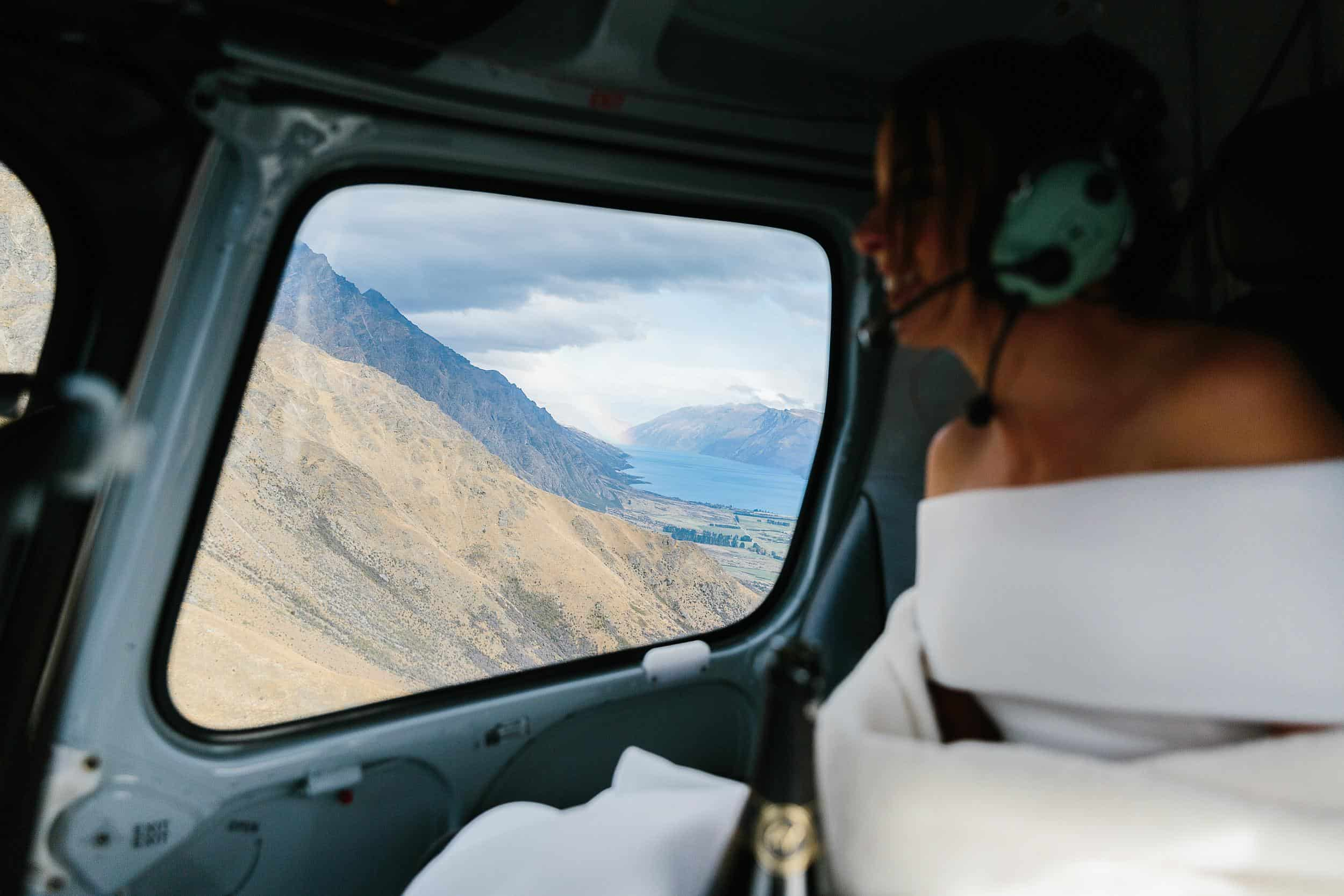 Bride looks out of window of helicopter