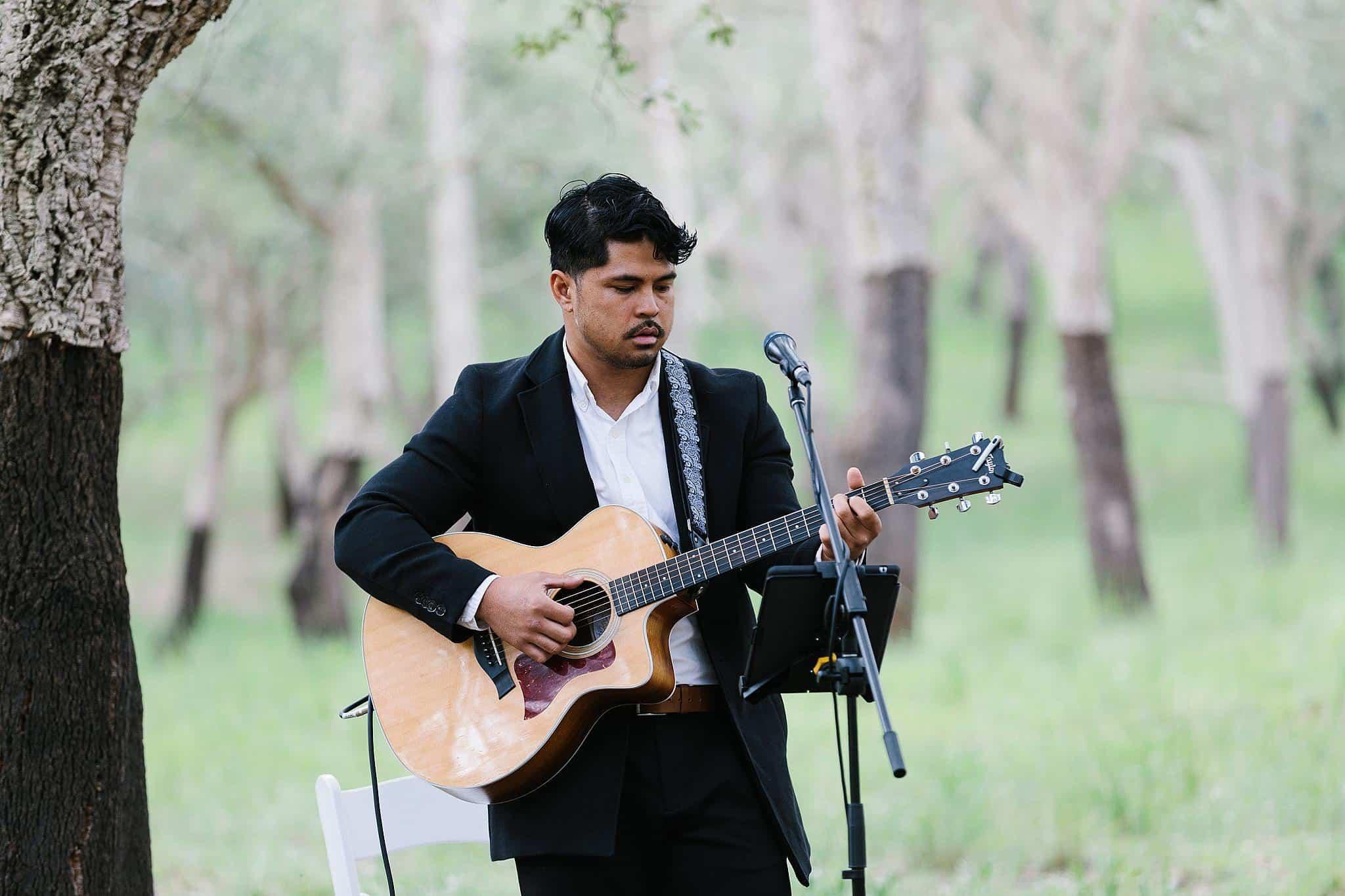 man plays guitar at wedding
