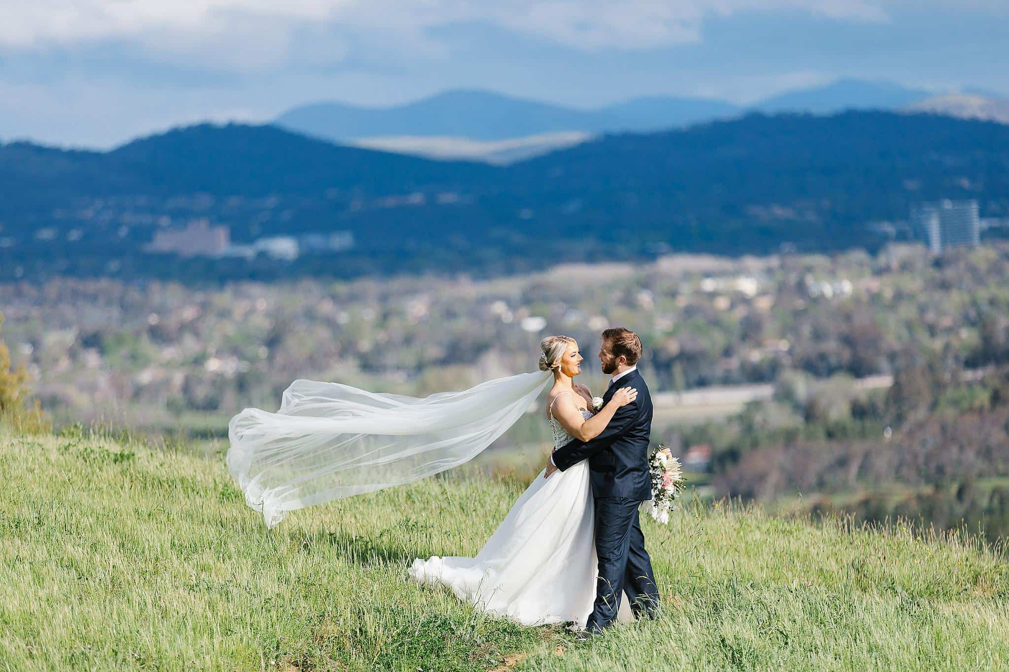 Bride and groom share intimate moment with mountains in the background