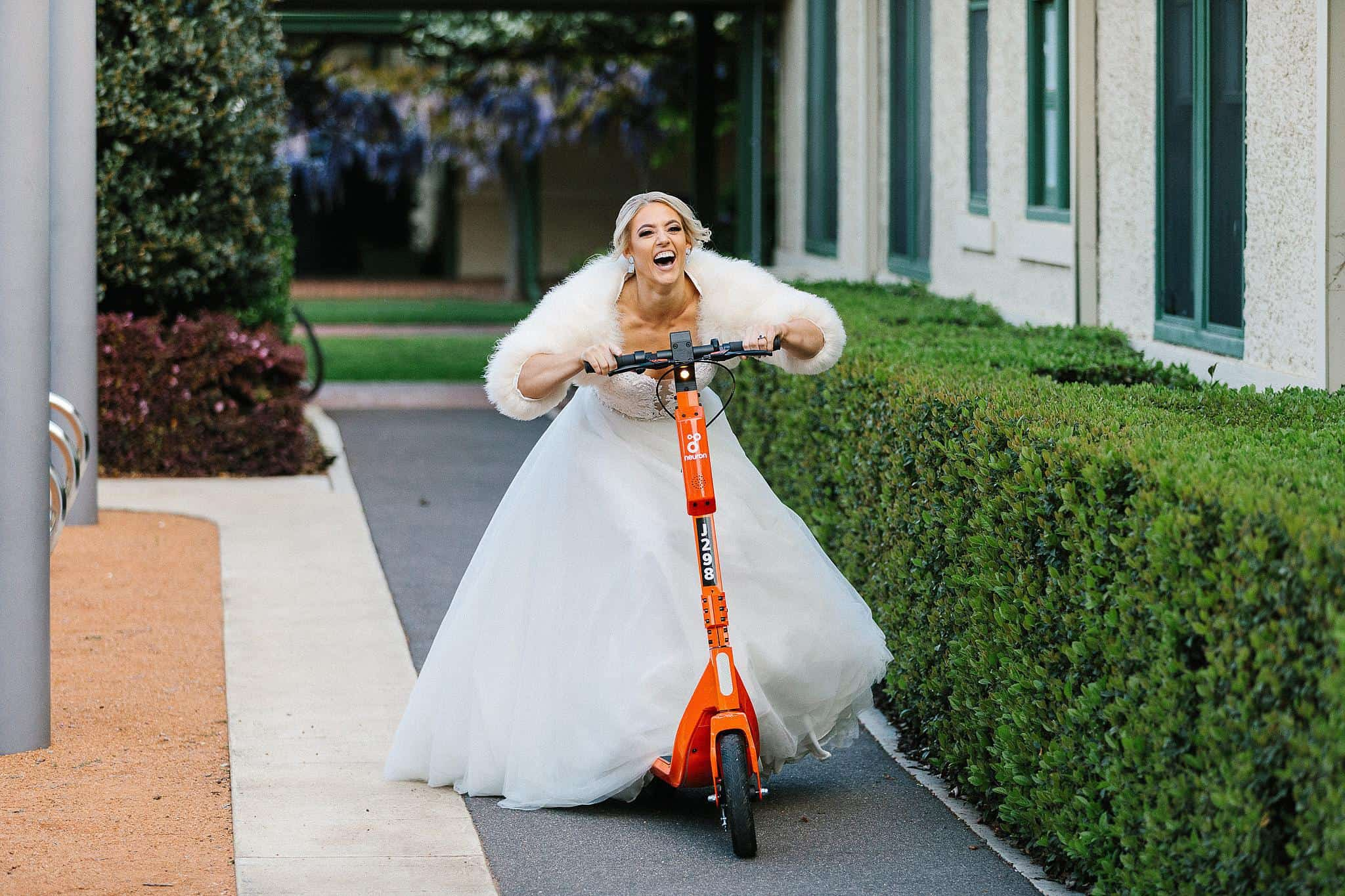 Bride rides scooter in wedding dress