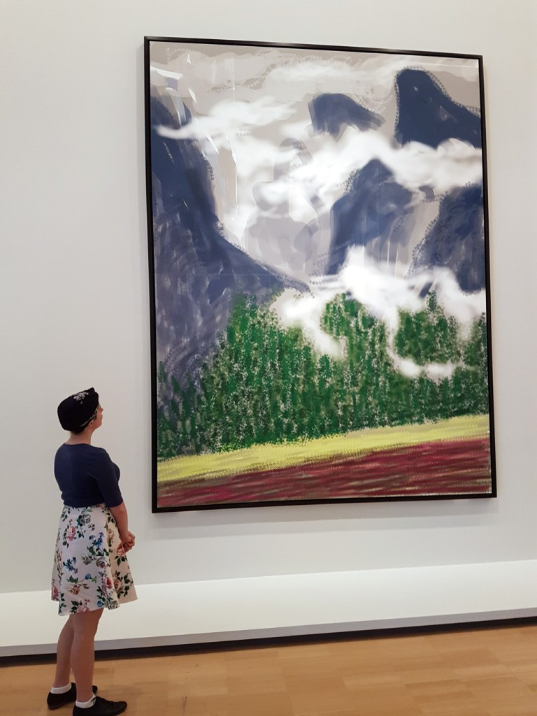 A visitor takes in one of David Hockneys large prints of a digital drawing of the Yosemites