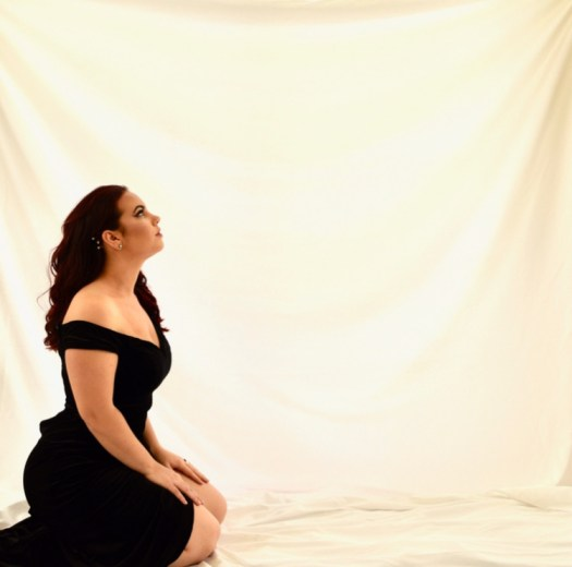 Giovanna Crescenzo wearing a black dress and kneeling.