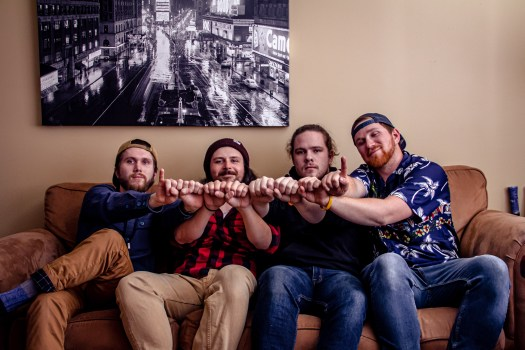 Old Old band members sit on a couch together and put their fists together.