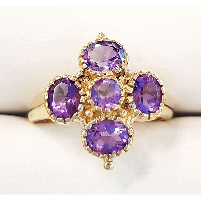 Gold ring featuring central round amethyst surrounded by four oval amethysts