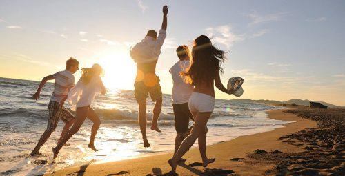 pessoas felizes pulando na praia