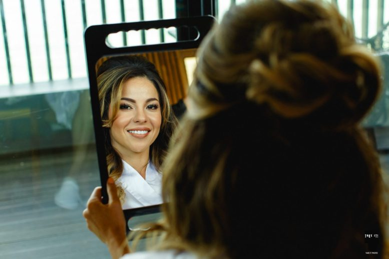 bride verifies her makeup for photo