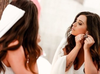 bride wears her ear rings for photoshoot