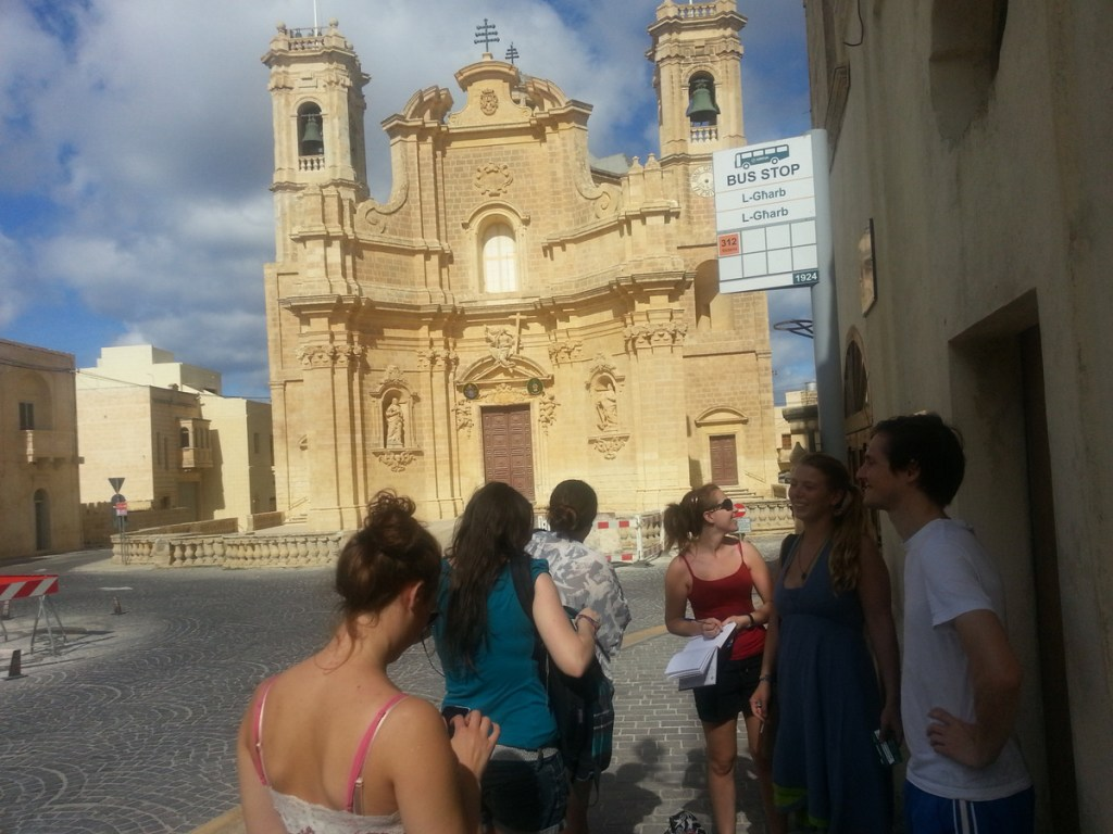 Bus station with game participants in front of the Gharb Church.