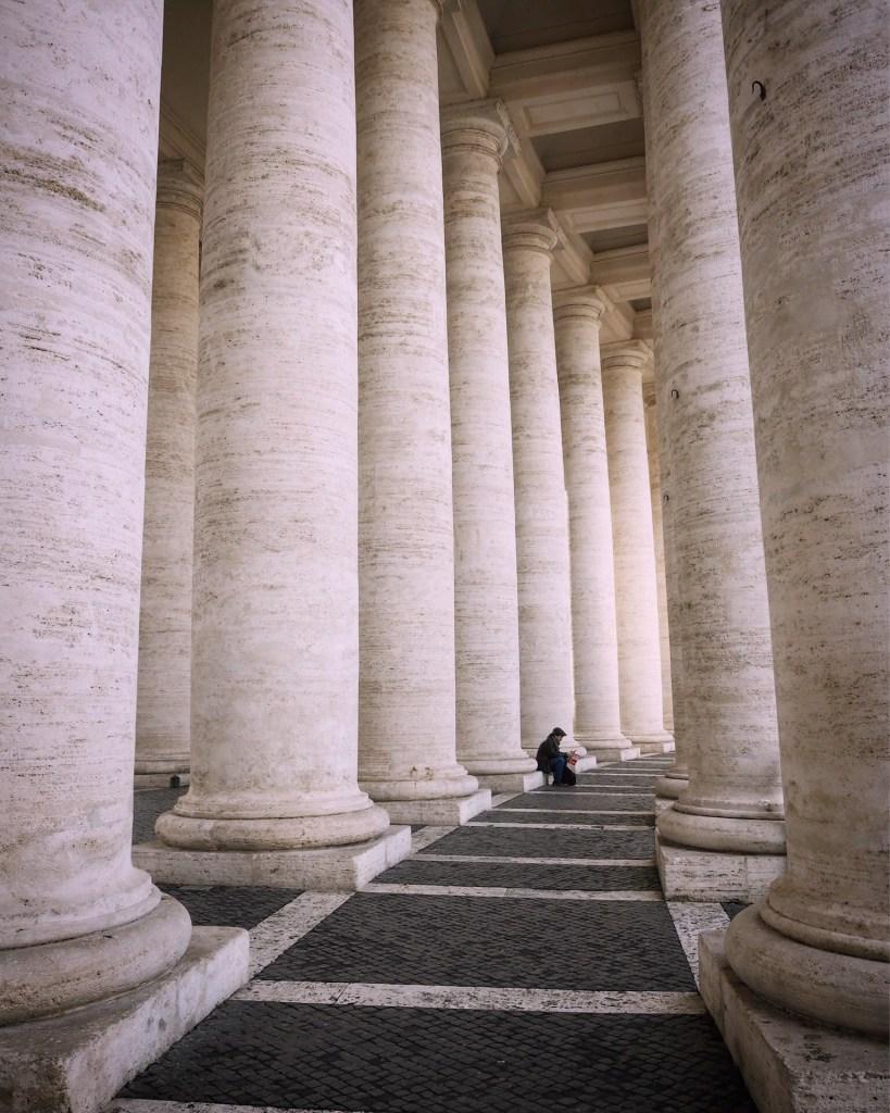 A man under the pillars near St Peter's basilica