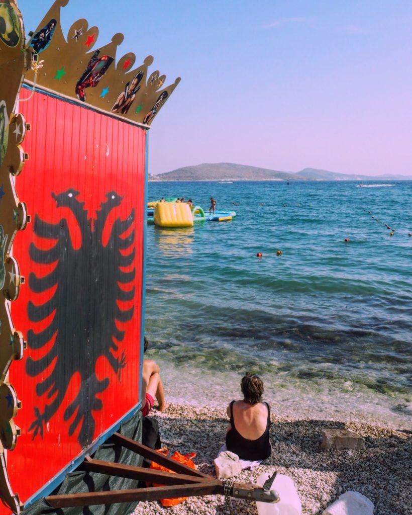 An Albanian flag painted near the beach in Saranda
