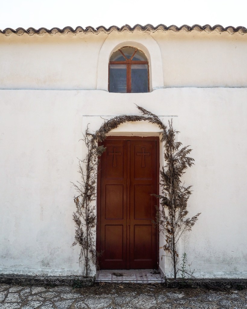 door to a church with dried leaves