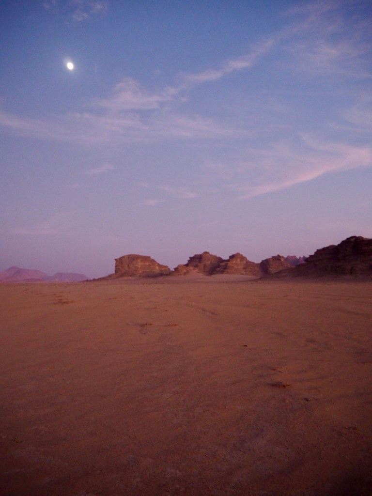 a tiny pale moon above the desert mountains