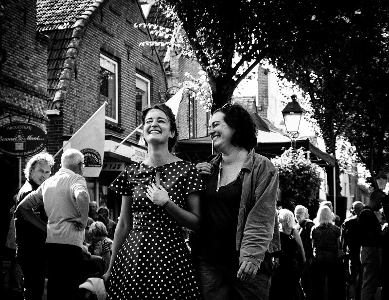 Twee lachende dames tijdens het Rock and Roll Street Terschelling festival in september 2016.