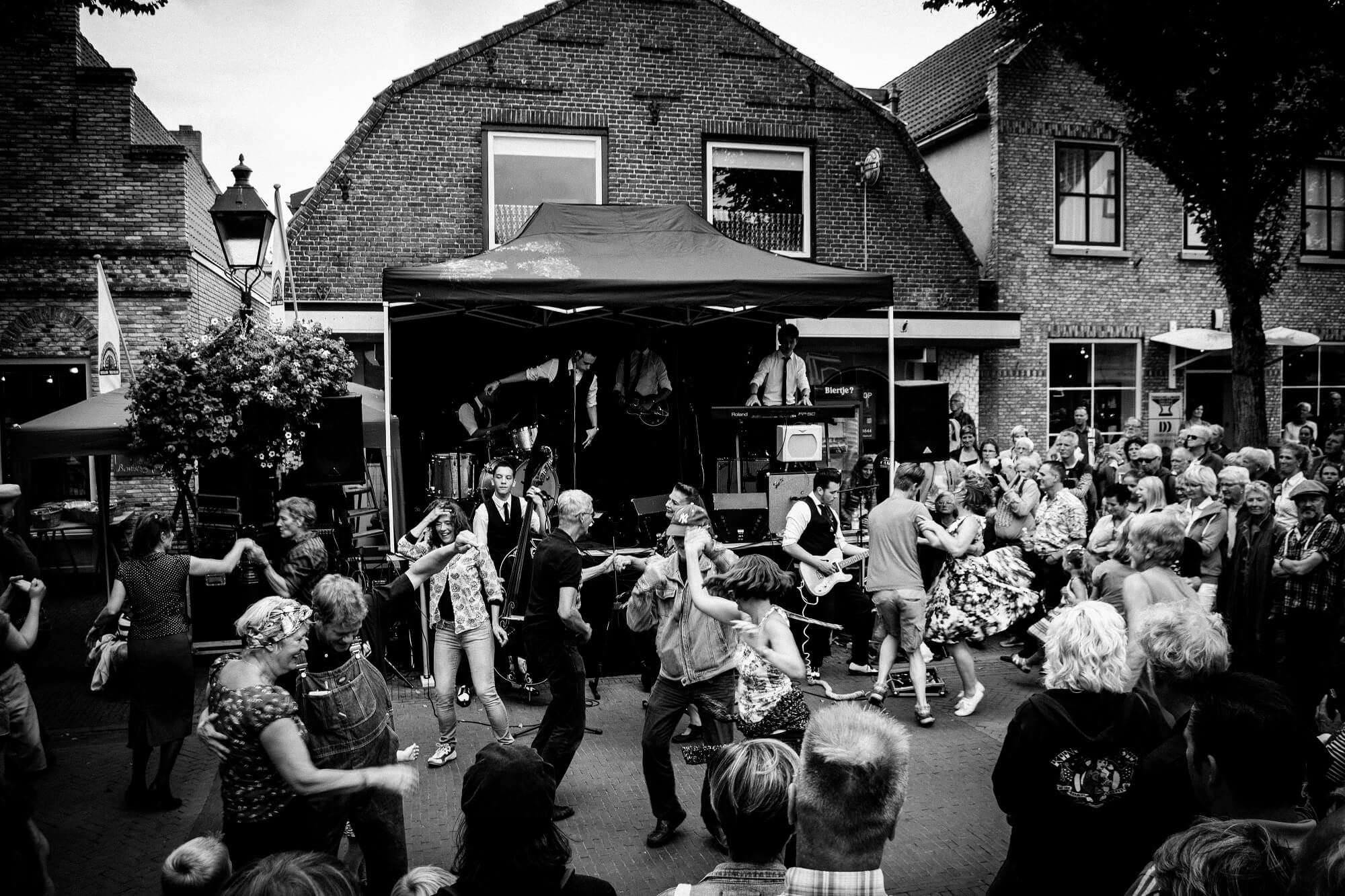 Mensen dansen op straat bij een optreden van de Hot Dogs Coverband op het Rock & Roll Street Terschelling festival 2016.