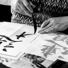 Japanse Kalligrafie workshop deelnemer maakt een teken met een kwast.