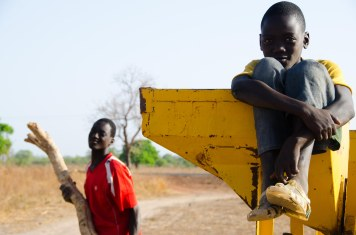 Musa and his brother play in a peanut shelling machine.