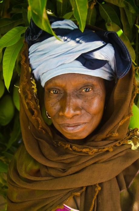 A Wolof lady underneath a mango tree at a wedding.