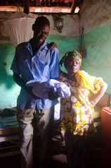 Aliou holds his newborn son with his proud mother Fatou beside him.